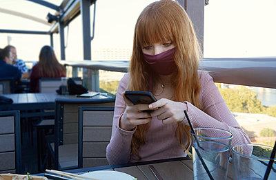 Mädchen mit Maske in einem Café - p1577m2263976 von zhenikeyev