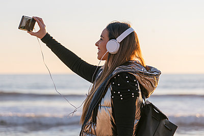 young woman listening to music on headpohones and taking a selfie, Matalascañas, Spain - p300m2243026 von Julio Rodriguez