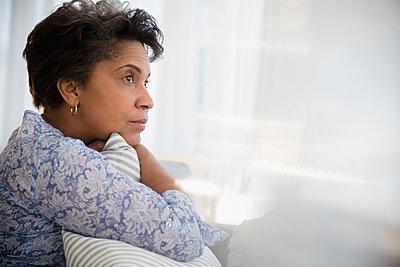 Pensive older Black woman clutching pillow - p555m1305425 by JGI/Jamie Grill