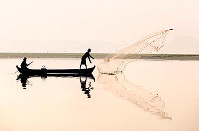 Fishermen on Taungthaman Lake in dawn mist, casting net near U Bein Bridge, Amarapura, near Mandalay - p871m819381 by Lee Frost
