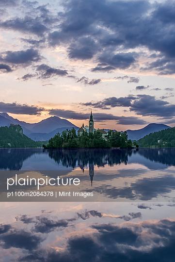 Village church and buildings reflected in still lake, Bled, Upper Carniola, Slovenia,Bled, Upper Carniola, Slovenia - p1100m2084378 by Mint Images