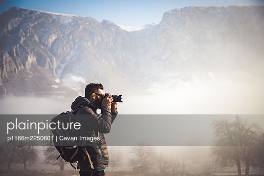 portrait of handsome man trekking in mountains in winter  outdoo - p1166m2250601 by Cavan Images