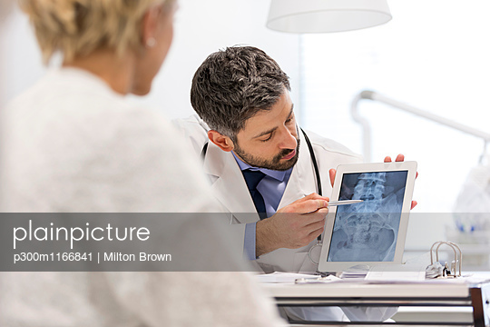 Doctor showing x-ray image on digital tablet to patient - p300m1166841 by Milton Brown