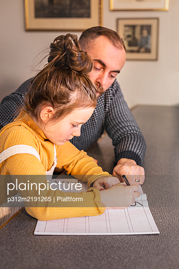 Father helping daughter with homework - p312m2191265 by Plattform