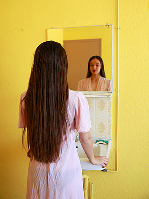 Woman is looking at herself in the mirror - p1105m2082554 by Virginie Plauchut