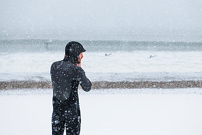 Man preparing to go surfing during winter snow - p1166m2177093 by Cavan Images