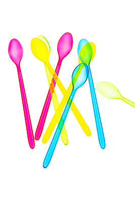 Coloured transparent plastic disposable spoons on white background - p1302m2045582 by Richard Nixon
