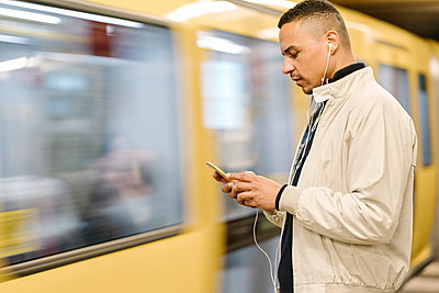 Man standing at underground station platform using earphones and cell phone, Berlin, Germany - p300m2143404 by Hernandez and Sorokina