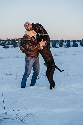 Playful Great Dane dog leaning on man in snow against clear sky - p300m2251275 by Eva Blanco