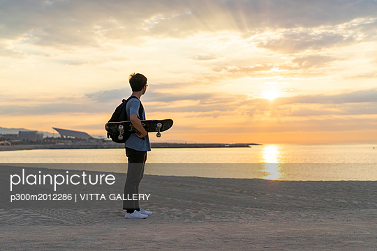 Young Chinese man with skateboard standing at the beach at sunrise - p300m2012286 von VITTA GALLERY