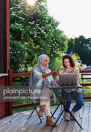 Female friends using laptop on patio - p312m2237128 by Pernille Tofte