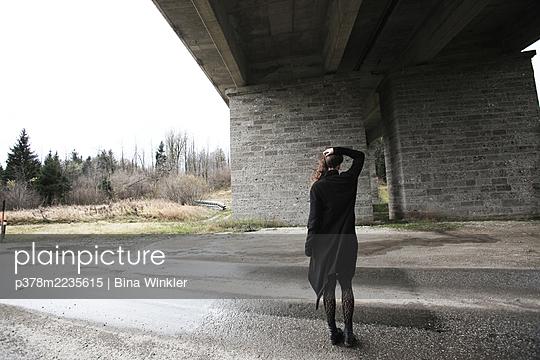 Woman standing under concrete bridge - p378m2235615 by Bina Winkler
