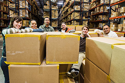Team portrait of multi-ethnic male and female warehouse workers in a large distribution warehouse full of products stored on pallets in cardboard boxes on large racks. - p1100m1575504 by Mint Images