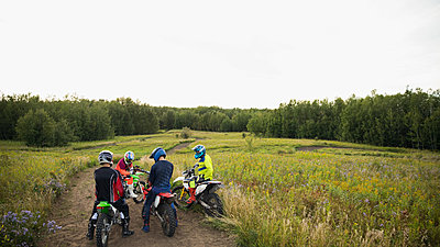 Male friends on motorbikes on rural dirt road - p1192m1500160 by Hero Images