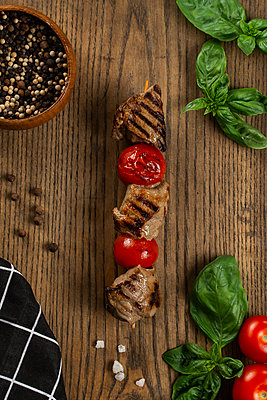 Grilled meat and tomato skewer on cutting board - p1427m2128276 by Aleksandr Kuzmin