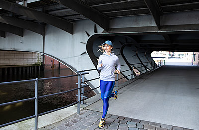 Woman jogging in Hamburg - p1678m2262237 by vey Fotoproduction