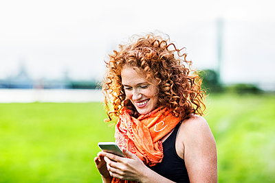 Portrait of happy young woman with curly red hair looking at cell phone - p300m2029191 by Jo Kirchherr
