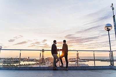 Gay couple on lookout above the city with view to the port, Barcelona, Spain - p300m2154488 by VITTA GALLERY