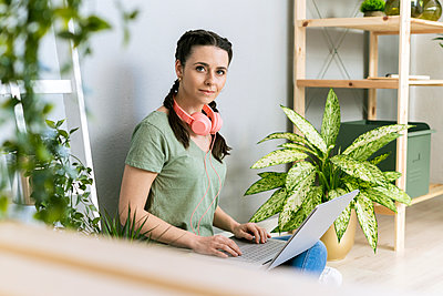 Young woman at home surrounded by plants - p300m2275418 von Giorgio Fochesato