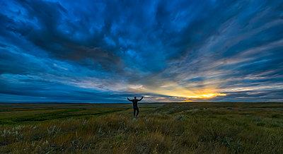 Man standing with his arms spread open at daybreak in Grasslands National Park; Saskatchewan, Canada - p442m1449115 by Robert Postma