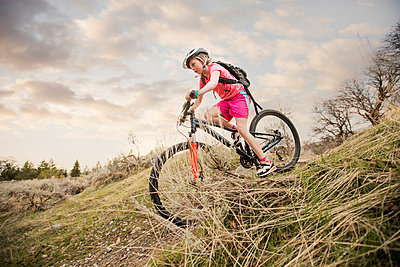 Caucasian girl riding bicycle on hill - p555m1490970 by Mike Kemp