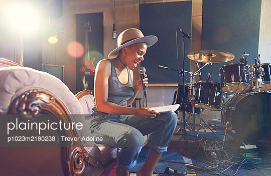 Young female musician singing and song writing in recording studio - p1023m2190238 by Trevor Adeline