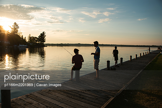 Father and sons fishing on dock of lake at sunset in Ontario, Canada. - p1166m2201969 by Cavan Images