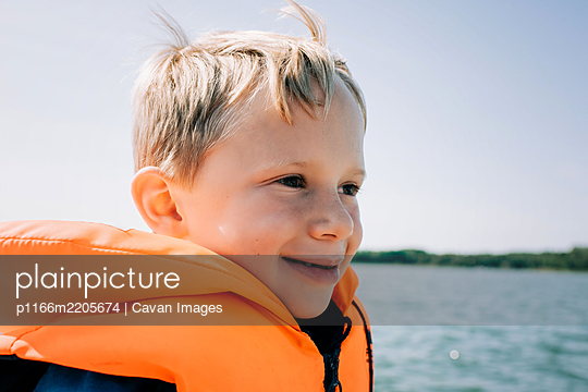 portrait of happy young boy sat in a boat in summer in Sweden - p1166m2205674 by Cavan Images