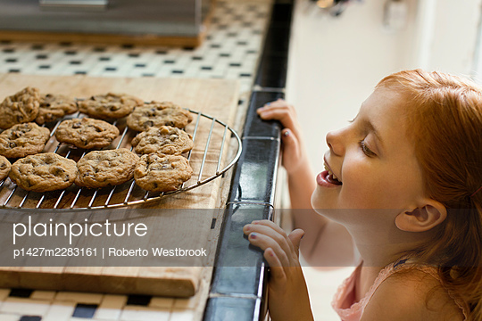 Girl peeking over kitchen counter at biscuits - p1427m2283161 by Roberto Westbrook