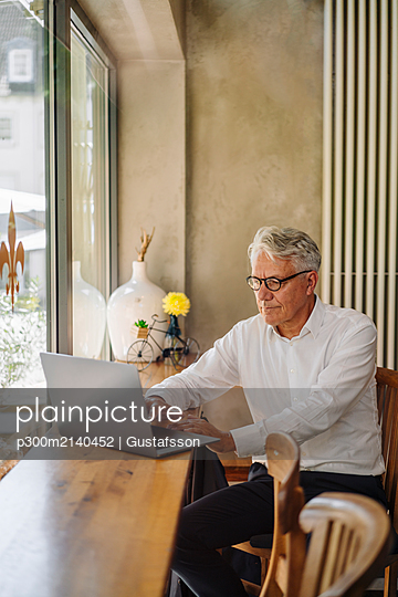 Senior businessman using laptop in a cafe - p300m2140452 by Gustafsson