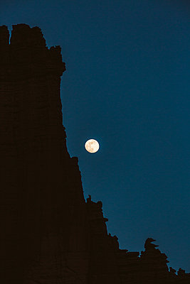 almost full moon rises over bizarre desert landscape at fisher towers - p1166m2174265 by Cavan Images