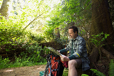 Man hiking checking map in woods - p1192m1149440 by Hero Images