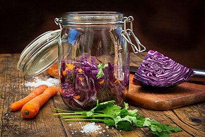 Homemade red cabbage, fermented, with chili, carrot and coriander, preserving jar on wood - p300m2042742 by Larissa Veronesi