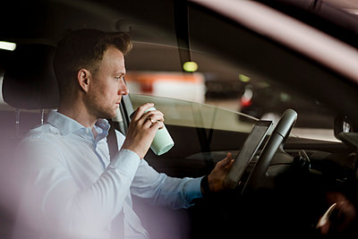 Businessman with coffee reading online on digital tablet in car - p300m2206572 by Daniel Ingold