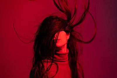 Woman tossing hair against red background - p300m2265349 by Ezequiel Giménez