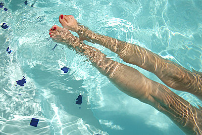 A woman's legs in a swimming pool - p3013537f by Stella