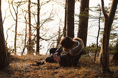 Woman using cell phone in forest - p312m1442797 by Cecilia Moller