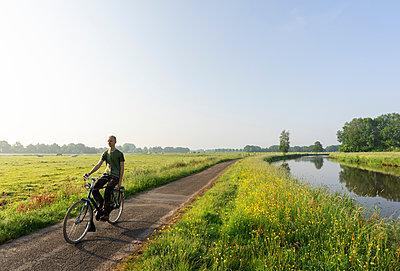 Boy cycling along Mark river in morning, Galder, Noord-Brabant, Netherlands - p429m2004561 by Mischa Keijser