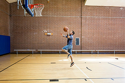 Tattooed man jumping and aiming ball toward basketball net on court - p924m1224794 by Raphye Alexius