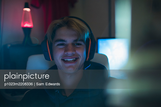 Smiling teenage boy in headset - p1023m2208336 by Sam Edwards
