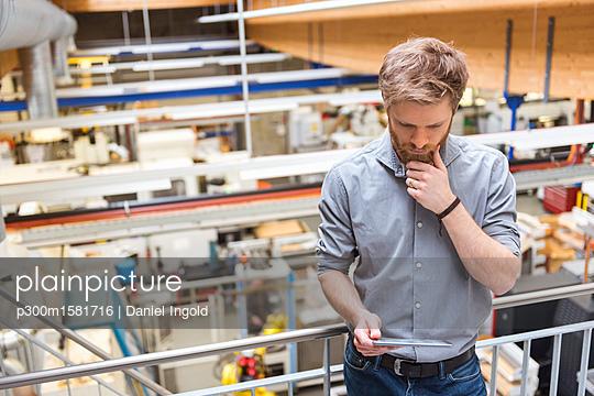 Businessman using tablet in modern factory - p300m1581716 von Daniel Ingold