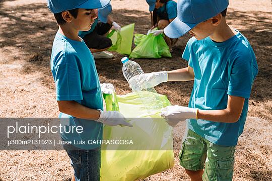 Group of volunteering children collecting garbage in a park - p300m2131923 von Jose Luis CARRASCOSA
