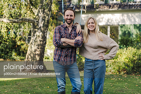 Proud home owners standing in their garden - p300m2166682 by Kniel Synnatzschke