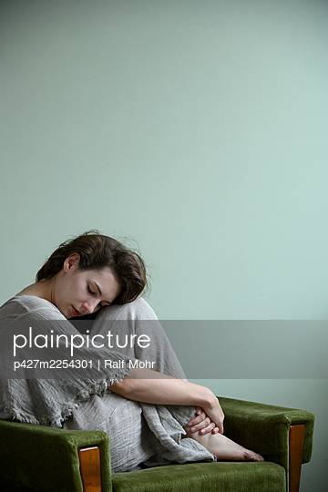 Pensive woman sitting on armchair - p427m2254301 by Ralf Mohr
