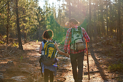 Young couple hiking with backpacks in sunny summer woods - p1023m2212825 by Trevor Adeline