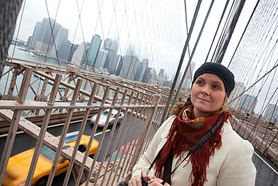 Young woman on Brooklyn bridge with yellow taxis on street at New York City, USA - p1025m788822f by Nicklas Blom