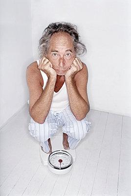 Älterer Mann auf einer Waage - p1207m1109467 von Michael Heissner