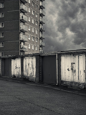 Run down garages in front of slum flats - p1280m2223561 by Dave Wall