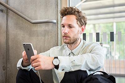 Student benutzt sein Smartphone und Kopfhörer - p1284m1452023 von Ritzmann