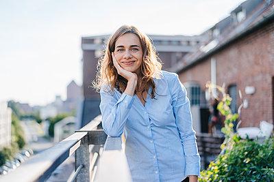 Businesswoman standing on her urban rooftop garden - p300m2070248 by Kniel Synnatzschke
